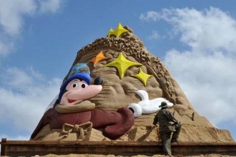 """A sand sculptor works on a masterpiece ahead of the 13th Zhoushan International Sand Sculpture Festival, which opens on September 24. This year's theme? """"Disney""""."""
