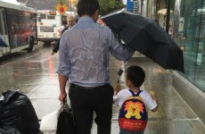 'Umbrella dad' is melting hearts all over the internet for selflessly sheltering his son