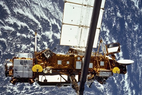 The STS-48 onboard photo of the Upper Atmosphere Research Satellite (UARS) in the grasp of the RMS (Remote Manipulator System) during deployment, from the shuttle in September 1991. The satellite is 35 feet long, 15 feet in diameter, weighs 13,000 pounds.