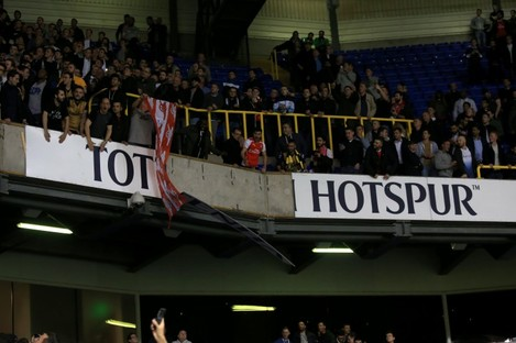 Arsenal fans tear down advertising signs in the stand after the team's 2-1 win at Spurs last night.
