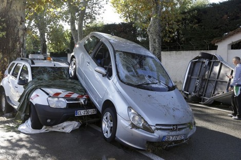 A man walks past damaged cars in Biot, near Cannes