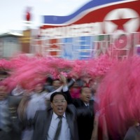 Loads of people are waving flags and flowers for Kim Jong-Un today