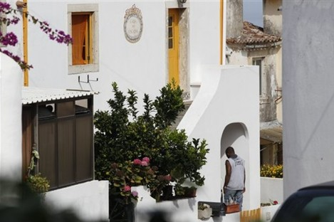 An unidentified man enters the house where neighbors said fugitive George Wright lived in Almocagema, near Lisbon Wednesday, Sept. 28, 2011.