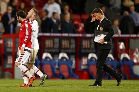 Manchester United's Wayne Rooney and Louis van Gaal walk off the pitch dejected at full time.