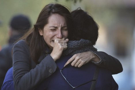 A woman cries as relatives and friends wait for victims to be identified following last week's nightclub fire.