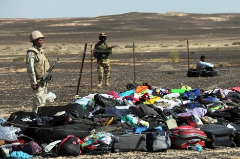 Egyptian Army soldiers stand near luggage and personal effects at the crash site.