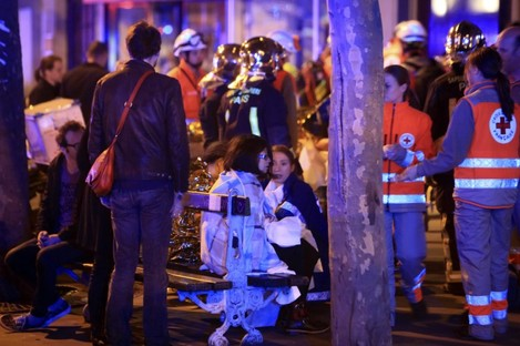 People rest on a bench after being evacuated from the Bataclan theatre in Paris.