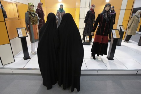 Head-to-toe veiled Iranian women look at mannequins in a women's dress show in Tehran.