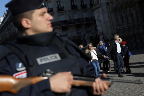 A policeman patrols in front of Notre Dame cathedral.