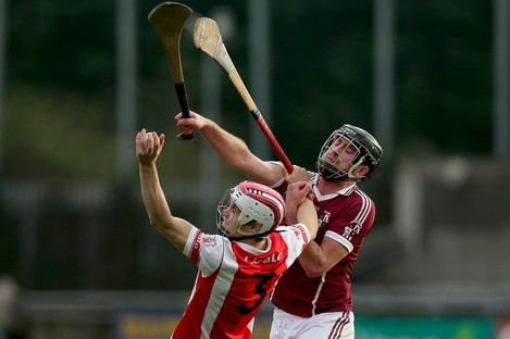 Cian O'Callaghan of Cuala and Clara's Conor O'Shea challenging for possession.