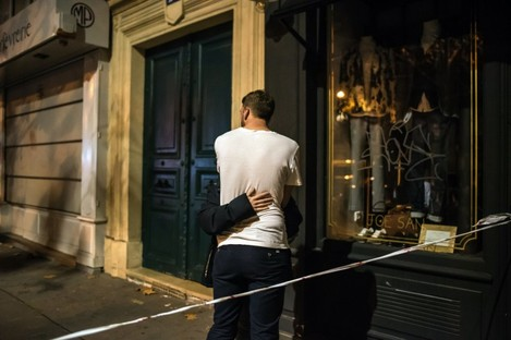 A couple conforts each other outside the Bataclan concert hall after a shooting in Paris.