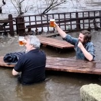 These two guys just kept on drinking even though the pub's beer garden was flooded