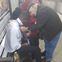 This lovely photo of an elderly couple helping a young man tie his tie is going viral