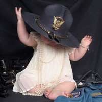This photo of a baby girl wearing her fallen mother's police hat has gone viral