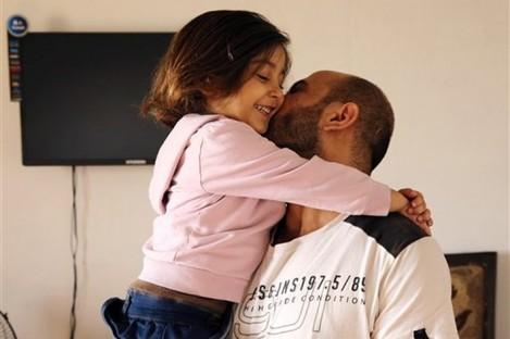 Abdul Halim al-Attar kisses his daughter Reem, 4, at their house in Beirut.