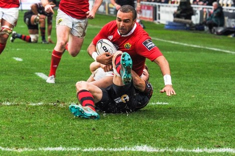 Dragons winger Tom Prydie wraps up Munster's Simon Zebo metres from the try line.