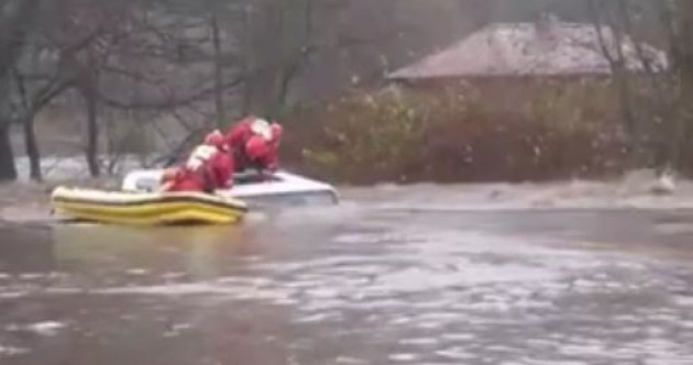 Watch: Driver pulled from sunroof after car trapped in rushing flood waters