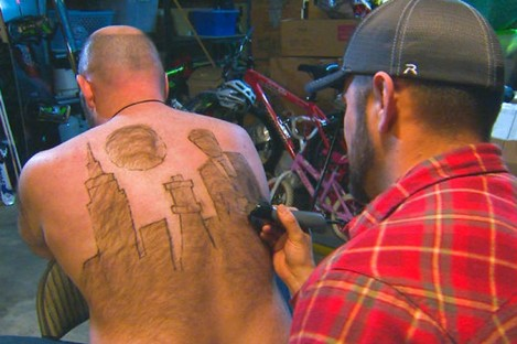 Mike Wolfe and Tyler Harding, who takes about an hour to trim designs on his back.