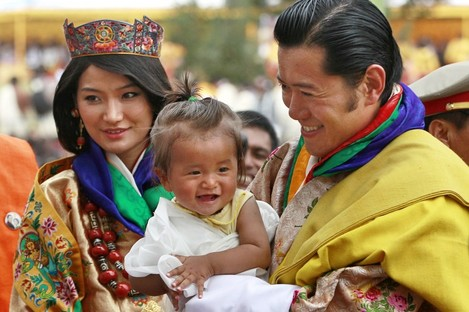 King Jigme Khesar Namgyal Wangchuck, right, holds a young child as he greets locals with Queen Jetsun Pema