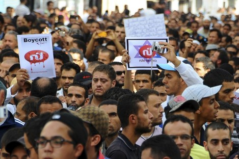Radical Islam followers demonstrate, some holding a picture of a defaced logo of a television channel, after Friday prayer in Tunis.