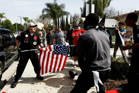 A Ku Klux Klansman, left, uses an American flag to fend off angry counter protesters.