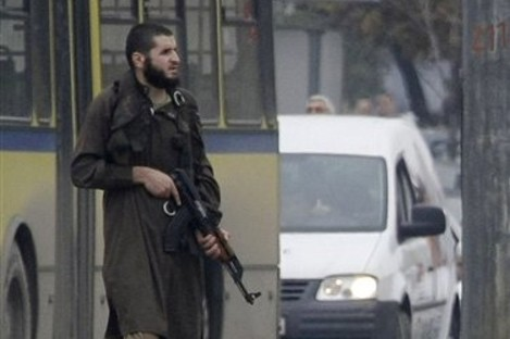 An gunman, identified as Mevlid Jasarevic, stands with an automatic weapon in the centre of the street in front of the US embassy in Sarajevo, Bosnia, Friday, Oct. 28, 2011.
