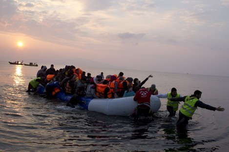 Volunteers help migrants on a dingy as they arrive at the shore of the northeastern Greek island of Lesbos.
