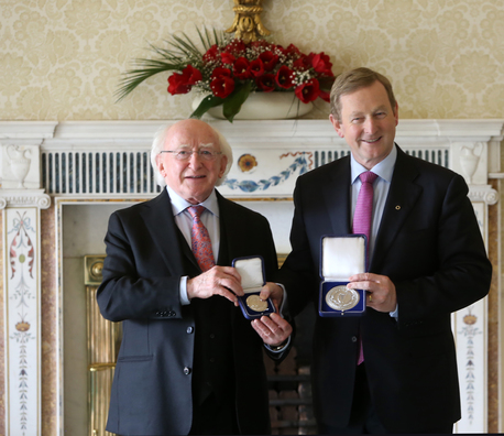 Newly re-elected Taoiseach Enda Kenny receives his seal of office from President Higgins.