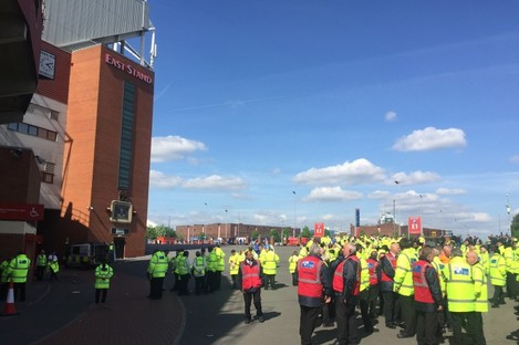 Old Trafford stewards wait outside after the stadium was completely evacuated.