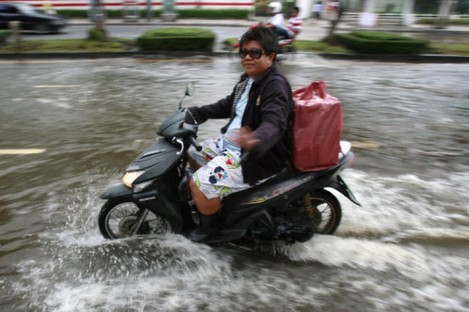 A Bangkok resident rides through rising floodwater in the capital on Friday.
