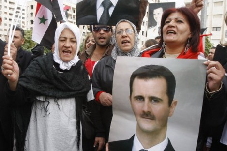 Supporters of President Assad gather outside the Syrian foreign ministry in Damascus yesterday.