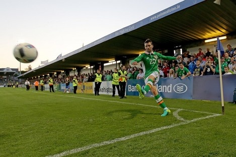 Wes Hoolahan takes a corner as the crowd looks on.