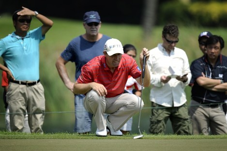 Padraig Harrington lines up his putt in the first round of the Singapore Open.