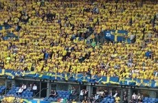 There's an Irish fan dressed as a leprechaun in the middle of the Swedish crowd