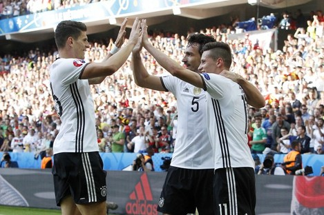 Julian Draxler, right, celebrates with his teammates Mats Hummels, center, and Mario Gomez after Germany beat Slovakia.