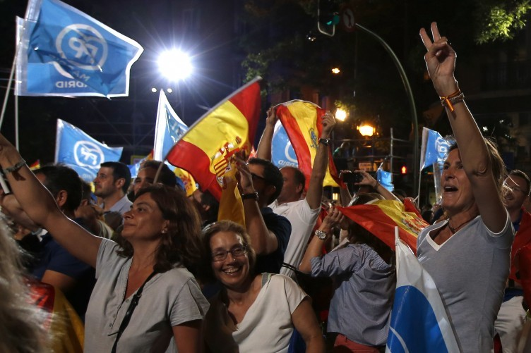 Followers of Spain's Popular Party celebrate the results of their party at the national elections in Madrid yesterday.