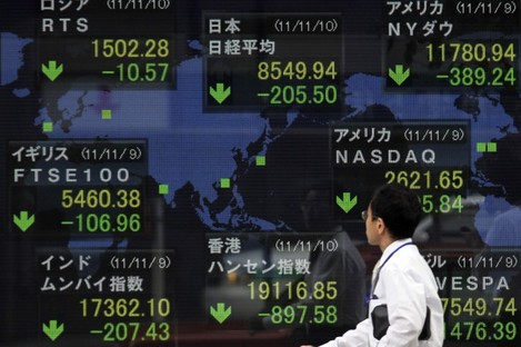 A man looks at an electronic stock board of a securities firm in Tokyo