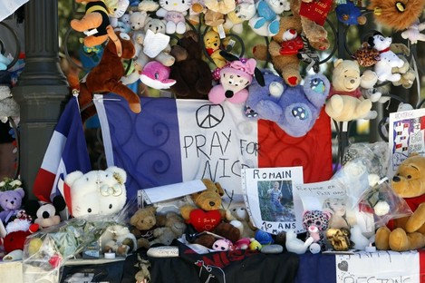 Baby dolls and teddy bears are placed at a memorial in Nice following the terrorist attacks.