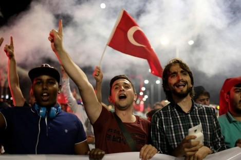 Pro-government supporters chant slogans and wave flags as they protest on Istanbul's iconic Bosporus Bridge on Thursday.