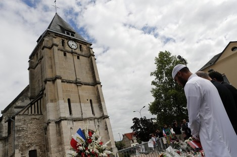 Muslim worshippers hold a minute of silence in front of the memorial at the Saint Etienne church in Saint-Etienne-du-Rouvray, Normandy.