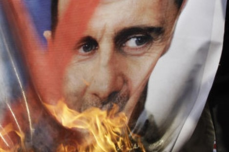 A portrait of Syria's president is set alight by anti-Assad protesters in Cairo on Saturday.