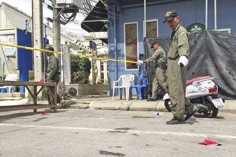 Investigators work at the scene of an explosion in the resort town of Hua Hi.