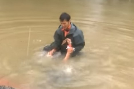 Woman being pulled from car in flood waters.