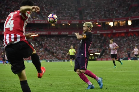 FC Barcelona's Lionel Messi, duels for the ball with Athletic Bilbao's Markel Susaeta.