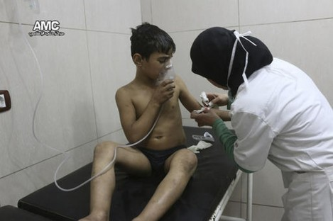 A nurse treating a boy suffering from breathing difficulties inside a hospital in Aleppo last week, after a suspected chlorine gas attack.