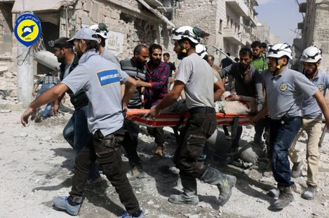 In this recent photo, provided by the Syrian Civil Defense White Helmets, rescue workers work the site of airstrikes in the al-Sakhour neighborhood of the rebel-held part of eastern Aleppo, Syria.