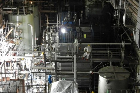 A worker climbs scaffoldings set up around a decontamination device at the Fukushima plant