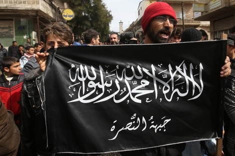 A man holds the flag of the Al-Nusra Front which is thought to have kidnapped the woman.
