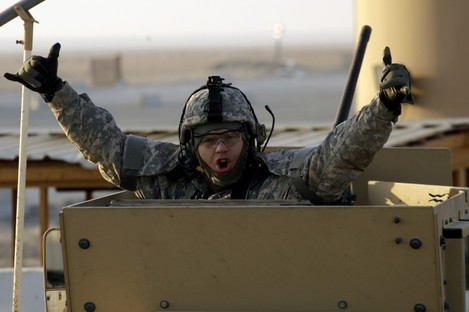 A soldier gestures from the gun turret of the last vehicle in a convoy at the Kuwaiti border