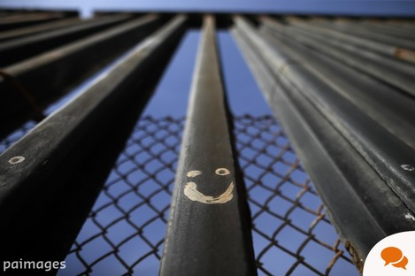 Graffitti adorns metal bars marking the United States border with Mexico.